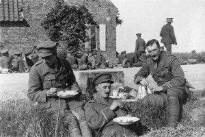 Officers of the 2nd Battalion Royal Warwickshire Regiment eating lunch while resting by the roadside.